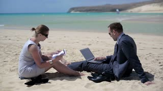 Businesspeople sit on beach and work