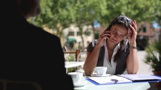 Businesspeople sitting at patio table outside with documents and cellphone