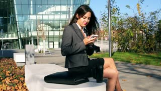 Businesswoman browsing internet on smartphone outside the building