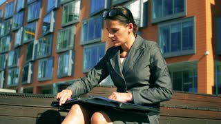 Businesswoman checking report and sitting in front of modern building