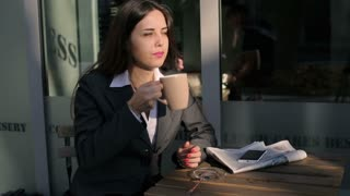 Businesswoman drinking coffee outside the cafe and using cellphone