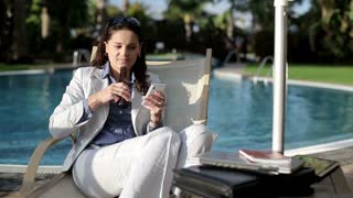 Businesswoman lying on sunbed with cellphone and drinking beer