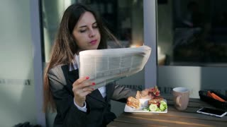 Businesswoman reading newspaper outside the cafe and looking to the camera