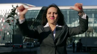 Businesswoman showing thumbs down to the camera outside the building