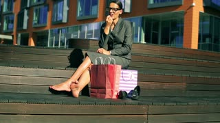 Businesswoman sitting and using red lipstick in front of modern building