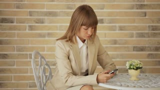 Businesswoman sitting at cafe and using mobile phone