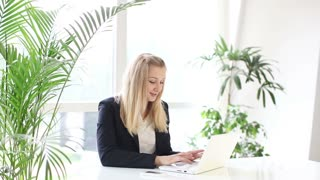 Businesswoman sitting at office table smiling talking on mobile phone and using laptop