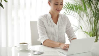 Businesswoman sitting at table and using laptop