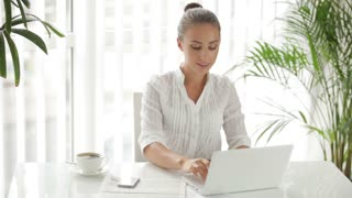 Businesswoman sitting at table using laptop and cellphone