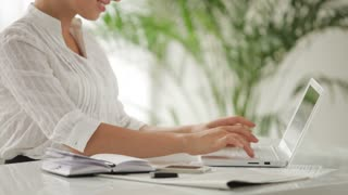Businesswoman sitting at table using laptop and writing in notebook