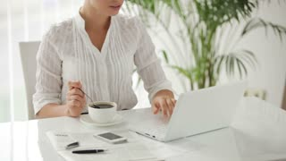 Businesswoman sitting at table with cup of cofee and using laptop with smile
