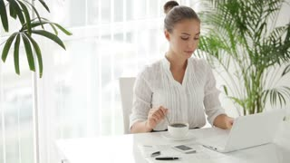 Businesswoman sitting at table with cup of cofee and using laptop