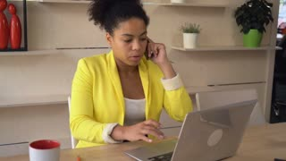 Businesswoman sitting at the working place with wooden table typing on the computer. Female using mobile phone and laptop talking with customer or client. Happy smile girl wearing in casual yellow