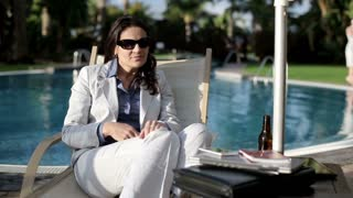 Businesswoman sitting by the poolside and getting bed news by cellphone