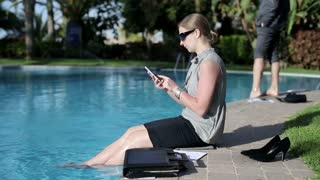 Businesswoman sitting by the poolside with cellphone