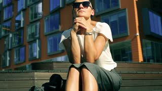 Businesswoman sitting in front of modern building and waiting