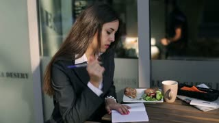 Businesswoman sitting outside the cafe and making notes