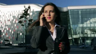 Businesswoman talking on cellphone and drinking coffee from thermal mug, steady