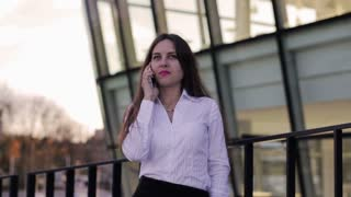 Businesswoman talking on cellphone and standing outside