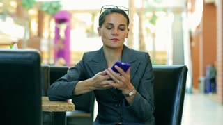 Businesswoman talking on cellphone in restaurant in modern place