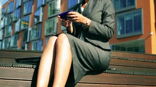 Businesswoman texting on smartphone and relaxing in front of modern building