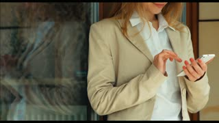 Businesswoman using cellphone and looking at camera. Zooming