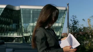 Businesswoman walking outside and looking at papers, steadycam shot