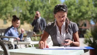 Businesswoman with cellphone working in cafe, outdoors