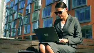 Businesswoman working on laptop and documents in front of modern building