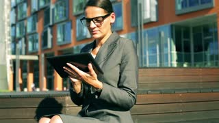 Businesswoman working on tablet and smiling to the camera