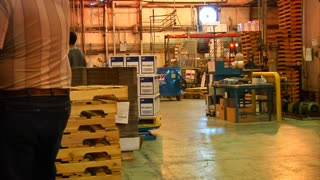 Busy Industrial Warehouse With Two Forklifts And Pallets