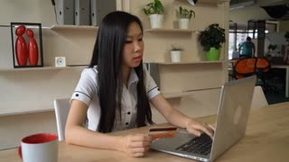 Busy multicultural worker paying by credit card via internet for purchases. Young vietnamese ordering some meal or booking tickets with debit card. Female typing security code on the laptop at the