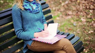 Busy student sitting in the park and doing notes