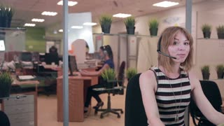 Call centre. Young woman with headset talks to a customer. Customer support concept