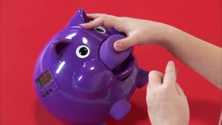Camera Move Up of Eight Year Old Girl Putting Money in Piggy Bank