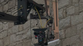 Camera On Crane Moves Through Stone Doorway