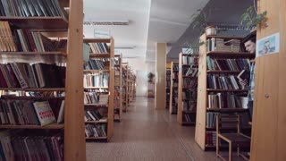 Camera quickly moves through the library passing bookshelves straight forward to white door in the end of hall