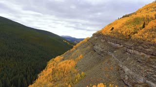 Aerial drone flight past cliffs and fall foliage in the Rocky Mountains