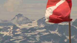 Canadian Flag Waving Over Snowcapped Mountains