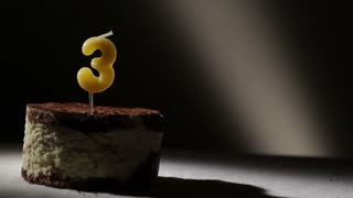 Candle three in tiramisu cake. Birthday vintage background.