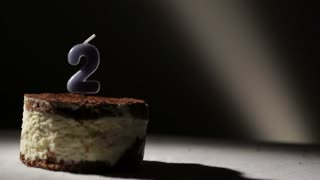 Candle two in tiramisu cake. Birthday vintage background.