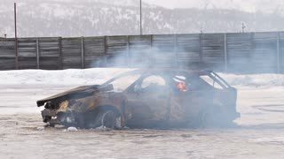 Car Burning in Icy Lot with Flames