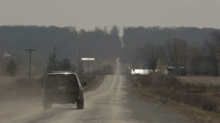 Car Driving Down Dusty Rural Road