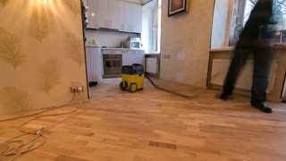 carpenter workers in green uniform cleaning room with a vacuum cleaner after installing wood parquet board during flooring work timelapse