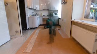 carpenter workers in green uniform installing wood parquet board during flooring work timelapse