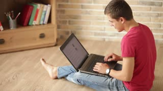 Casually dressed young man sitting on floor and using laptop