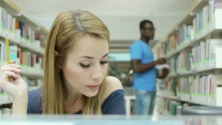 Caucasian female college student reading book in library, with african american man taking book from shelves in background