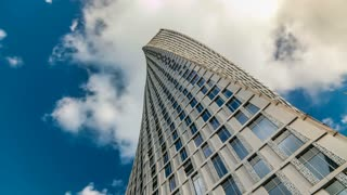 Cayan Tower timelapse (known also as Infinity Tower) in Dubai Marina. Perspective view from bottom to cloudy blue sky, The tower is world's tallest high rise building with a twist of 90 degrees - 306