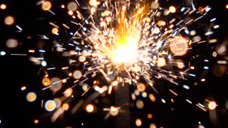 Center positioned orange sparkler against dark background. Super slow motion shallow focus video