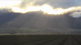 Central California Farmland Time-Lapse. Central California farmland with clouds and sun, shot in timelapse in late afternoon. Beams of sunlight shine through the cracks in the clouds. Rendered in UltraHD 4K from high resolution stills.